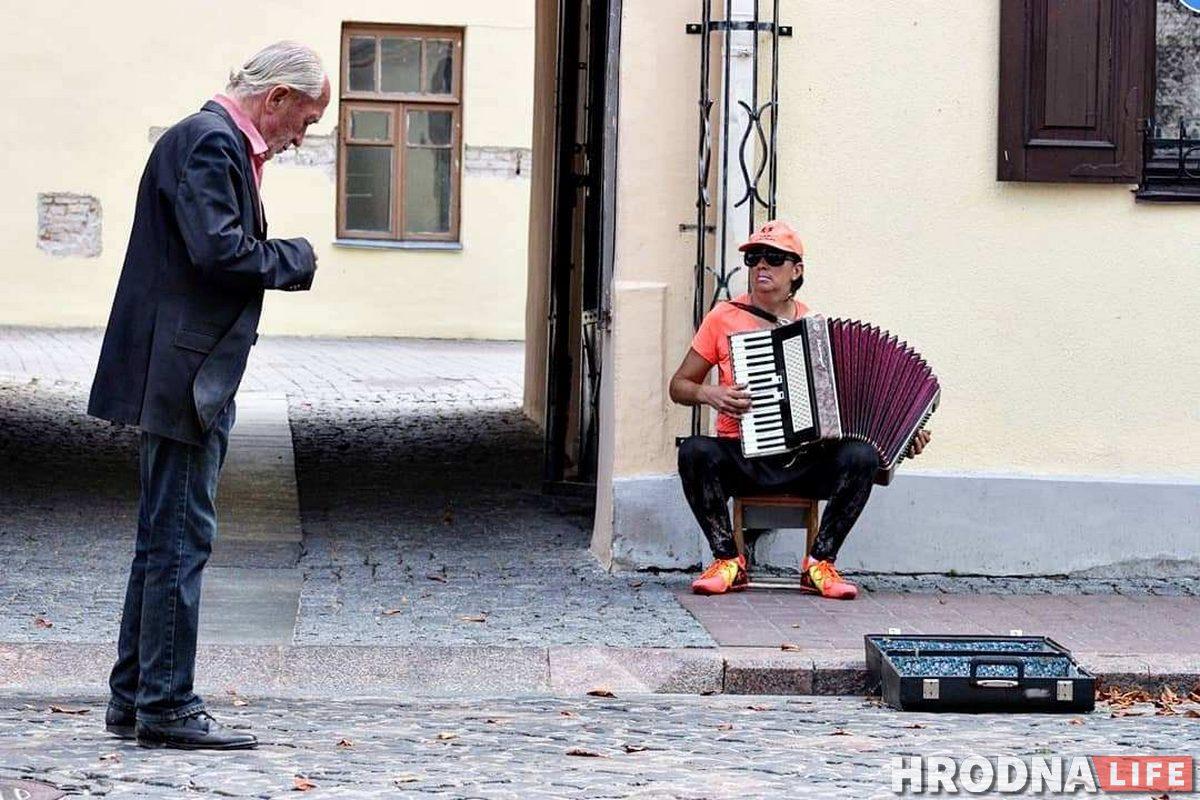 Станислав Свистун кидает деньги другому уличному музыканту - аккордеонистке Лене. Фото: Руслан Кулевич